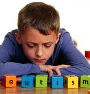 Autistic boy spelling out autism using alphabet blocks. Autism is a condition in which a child does not display the normal responses to words, faces and toys. The child is withdrawn and usually has difficulty coping with social situations, due to a limited understanding of the actions of others. However, autistic children often have excellent pattern recognition and numerical skills. The causes of autism remain unclear.